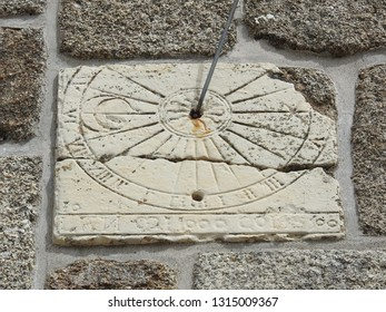 Vertical stone sundial on the wall of a medieval church built in the 11th century at the village of Nasbinals in Aubrac, Lozere, southern France. Detail of carved sun, moon, Roman numerals, and gnomon