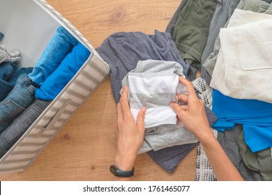 Vertical storage of clothing, Marie Kondo tidying up method, room cleaning concept. Woman hands tidying up and sorting clothes in basket. Top view