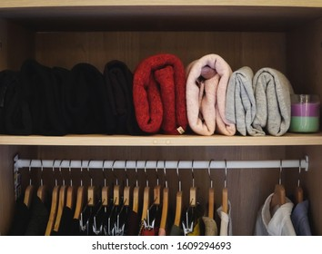 Vertical storage of folded blouses on closet shelf - tidying up and organizing your clothes and home - minimalism concept