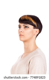 Vertical studio portrait. Beautiful young woman with trendy highlighted short pixie hairstyle on white background, looking sideways.