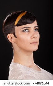Vertical studio portrait. Beautiful young woman with masculine shiny highlighted short pixie hairstyle on black background looking sideways