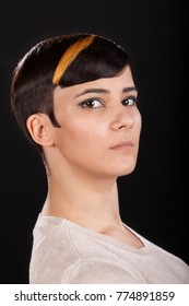 Vertical studio portrait. Beautiful young woman with masculine shiny highlighted short pixie hairstyle on black background looking at the camera