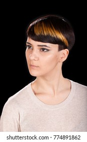 Vertical studio portrait. Beautiful young woman in her 20s with trendy highlighted short pixie hairstyle on black background looking sideways. Black background.