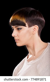 Vertical studio portrait. Beautiful young woman with trendy highlighted short pixie hairstyle on black background. Profile view