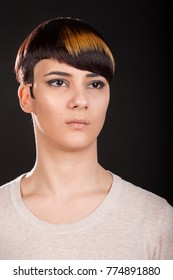 Vertical studio portrait. Beautiful young woman with trendy highlighted short pixie hairstyle on black background