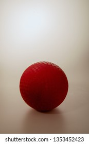 Vertical studio shot of red rubber playground ball (as used in dodge ball, handball, kickball, schoolyard and gym games) on gradated white background, with dramatic lighting, room for copy or text