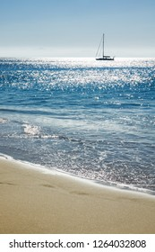 vertical summer or travel background with sand of the beach, blue sea and silhouette of a sailing boat in bright sunlight, Lanzarote, canary islands, Spain, Euope