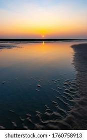 Vertical sunset with sand ripples on Oostende (Ostend) beach, West Flanders, Belgium Coast.