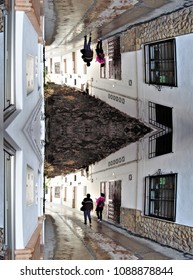 Vertical symmetrical photograph of tourists walking through the town of Setenil, with its famous streets under the mountain,
