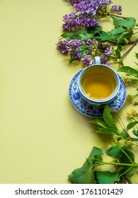 vertical template: chinaware, green jasmine tea and lilac flower blossom on yellow background