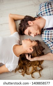 Vertical top above high angle view photo pair beautiful he him his macho she her lady just married honeymoon look gentle eyes overjoyed lying close faces in love apartments flat bright room indoors