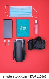 A vertical top view of a mask, hand sanitizer  smartphone, ear pads, passport holder, camera, and drone on a red background