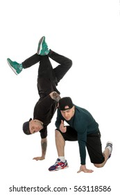 vertical of two handsome guys in casual clothes dancing modern dance in studio. break dancers isolated on white background. Men posing in studio in casual clothes.