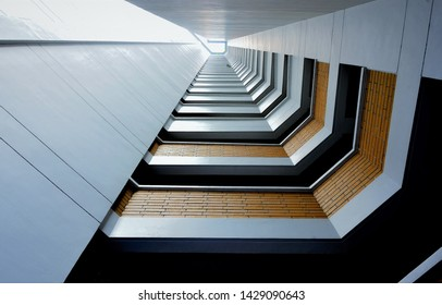 Vertical view up air well of apartment building in Singapore with strong geometry and architectural detail edited with blue filter
