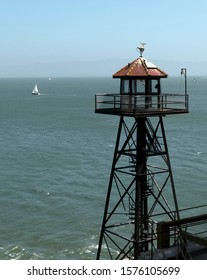 Vertical view of the Alcatraz guard tower with a sailing boat on the background