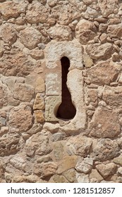 vertical view of an arrow slit in the stone wall of a castle