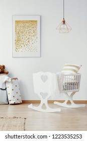 Vertical view of bright baby nursery with white crib and golden painting on the empty white wall