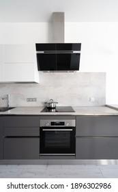 Vertikale Sicht auf eingebaute Geräte, Spülbecken, Backofen, Herdhaube, Elektroherd. Moderne Küche mit weißen Schränken, Marmordecke, Saucepan auf Induktionsglas-Keramikoberfläche. Kochnahrungskonzept