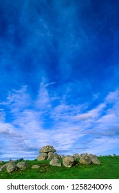Vertical view with Carrowmore Tomb 7 in the foreground, the most intact example of dolmen located in the oldest megalithic complex of Ireland, near Sligo, landscape with blue sky and clouds