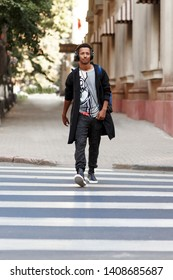 Vertical view. Cheerful guy walking on lesson with atitudine on the crosswalk listeng a music.