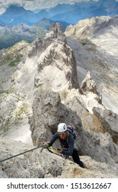 Vertical view of a cool young attractive mountain climber checks her mobile phone while climbing a Via Ferrata in the Dolomites