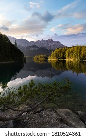 Vertical view of Eibsee mountain lake with sunlit islands in the morning sun