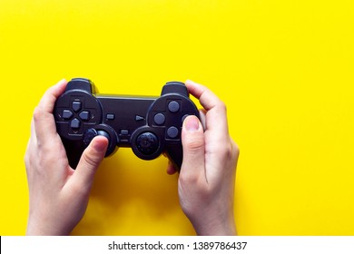 Vertical view of hands with gamepad. Gaming concept. Retro styled gamepad from 90s.