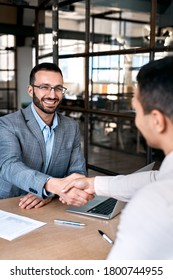Vertical view of happy businessman in formalwear sitting behind table in office, shaking hands with new employee after good interview