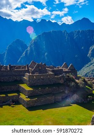 Vertical view of Machu Picchu old buildings, with rays of sun and mountains in the background