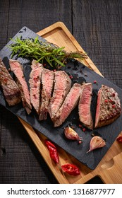 Vertical view on a juicy beef steak, grilled with traditional seasoning: sea salt, peppercorn, garlic, on a slate, served with fresh rosemary, thyme, chilli, on a dark wooden table, close up