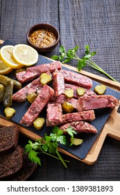 Vertical view on slices of aspic of meat mix, served with pickles, lemon, parsley, mustard with slices of rye bread on a black slate close-up