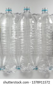 vertical view of a Pack of standing of empty mineral water Bottles  without caps just with the blue sealing ring on a white background. Reuse, Eco-Friendly, Environment, Conservation, Sustainable