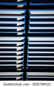 A vertical view of rich blue sky peaking through slats of roofing fin on high building.