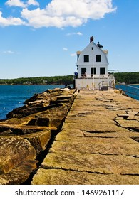 Vertical view of Rockland breakwater lighthouse and rock paved path Maine usa