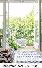 Vertical view of room with open balcony door, real photo