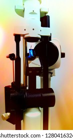 Vertical view of slit lamp and tonometer against warm orange background