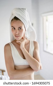 Vertical view of smiling young adult female looking at mirror, checking her skin and standing in white bathroom with towel on head