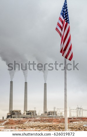 Vertical view of smoking smoke stacks of a generating station at the Navajo reservation, Arizona, USA. Smog and air polluting power plant in the background, United States flag in the foreground.
