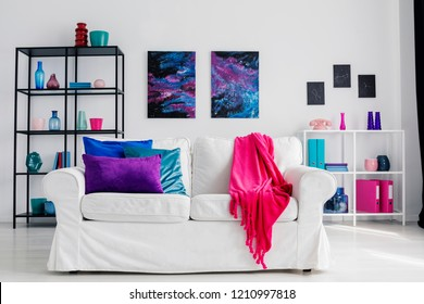Vertical view of stylish living room with comfortable white couch with pink blanket and blue and purple pillows, galaxy graphics on the wall and metal shelves with accessories, real photo