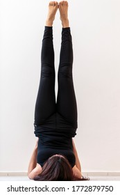 Vertical view of supported legs up the wall Viparita Karani asana. Young woman doing yoga pose, supporting hips with hands, projecting legs upright with back, shoulders, and elbows on the ground