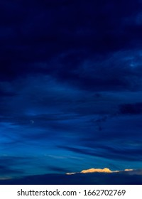 Vertical vivid blue nightscape of dramatic layered blues, pale moon and small bright cloud accent.
