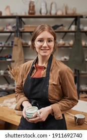 Vertical waist up portrait of young female potter looking at camera while posing in workshop, hobby and small business
