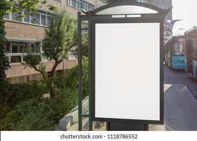 Vertical white billlboard among trees in the bus stop on the pavement by the street by two busses in the city with