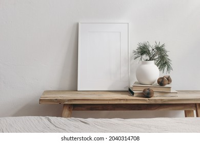 Vertical white picture frame mockup. Vintage wooden bench, table. Modern vase with pine tree branches. Paper baubles on pile of books. White wall background. Scandinavian interior, neutral color.