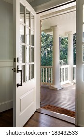 Vertical wide  shot of an open, wooden front door from the interior of an upscale home with windows.