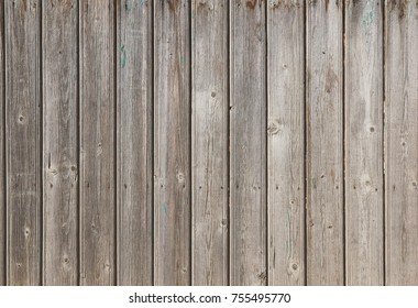 Vertical wood plates. Old abstract grunge background with wooden fence with traces of crack, scratches, damage. Rough dirty stained surface barnwood.