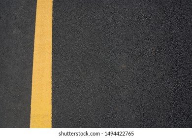 A vertical yellow paint line on black asphalt texture top view text space