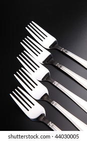 vertically isolated forks on a black background
