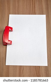 Vertically oriented blank sheet of white office paper is inserted into slot of steel office hole puncher, red colored, mock up with copy-space.