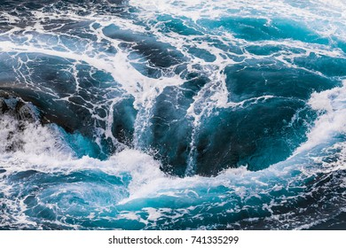 vertiginous, swirling foamy water waves at the ocean photographed from above